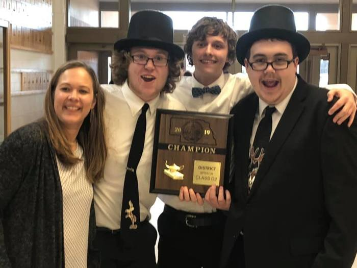 part of the speech team with the district champion plaque